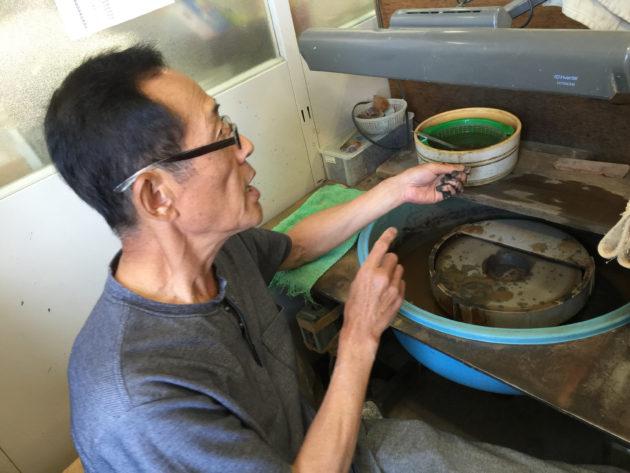 清水幸雄氏が手摺りで宝石を研磨します